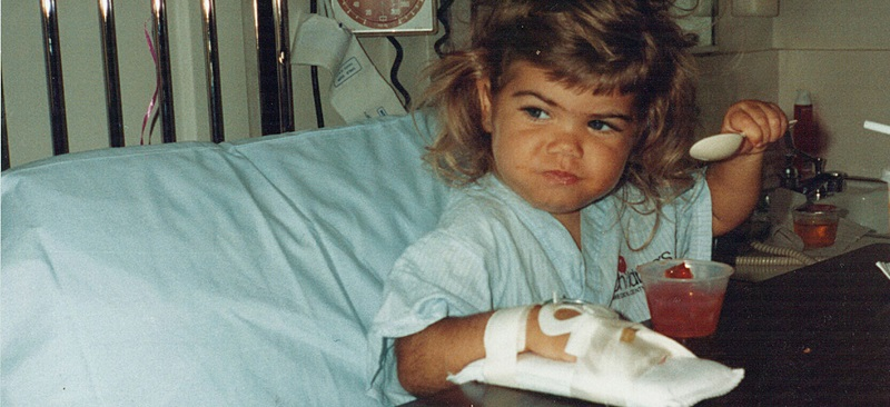 Kendra Plumley in a hospital bed, shortly after getting a heart transplant at 21 months old.