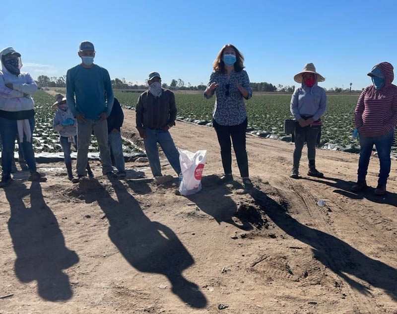 Gloria Giraldo (center) of Latino Health Access discusses COVID-19 vaccine safety and effectiveness with agricultural workers at a farm in Irvine, California. (Photo courtesy of Latino Health Access)